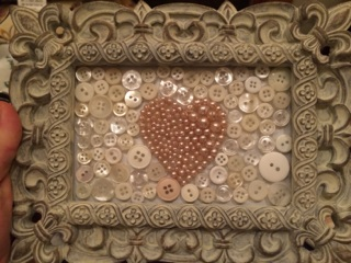 "This is probably my favorite. There is white cardstock inside the frame and then I used the beads on a cheapy, pink ""pearl"" necklace to make a heart (I drew on the back side of the glass using a dry erase marker first to trace the heart shape), and then filled in the background with white buttons. Everything was stuck on using hot glue."